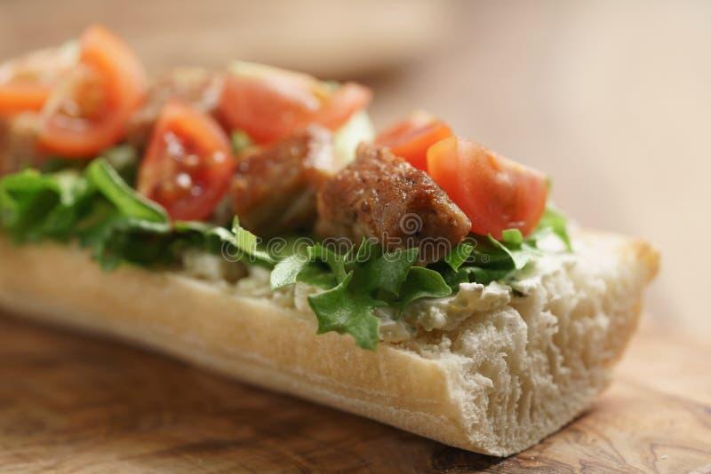 Bocadillo abierto con cerdo, salat y tomates fritos en la tabla de cocina imagen de archivo libre de regalías