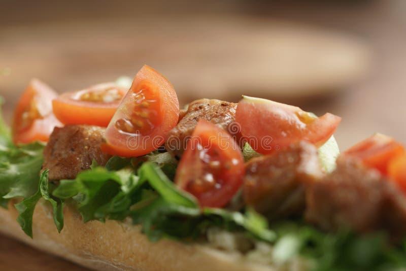 Bocadillo abierto con cerdo, salat y tomates fritos en la tabla de cocina foto de archivo