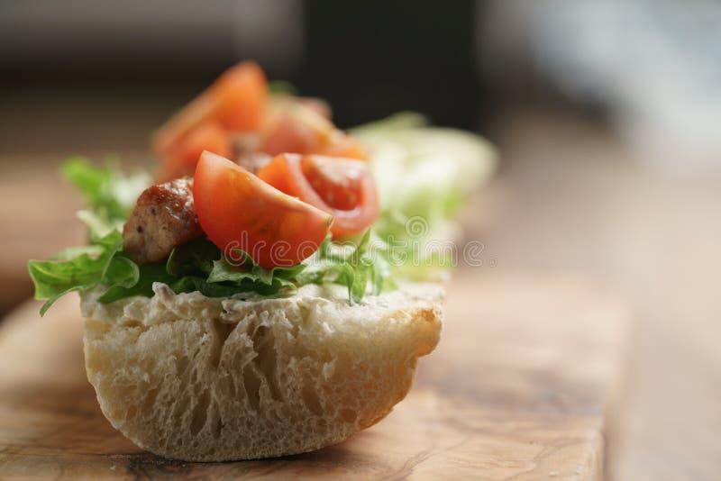 Bocadillo abierto con cerdo, salat y tomates fritos en la tabla de cocina imagen de archivo