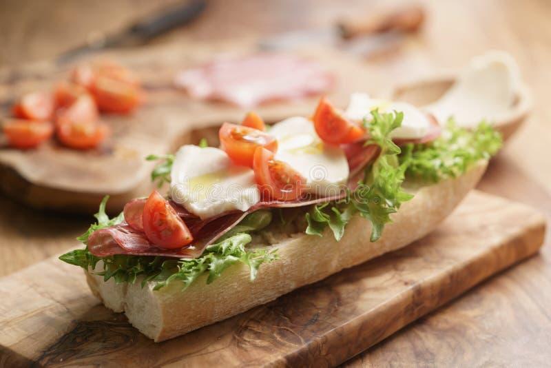 Bocadillo abierto con el prosciutto, la mozzarella y los tomates en la tabla de cocina foto de archivo