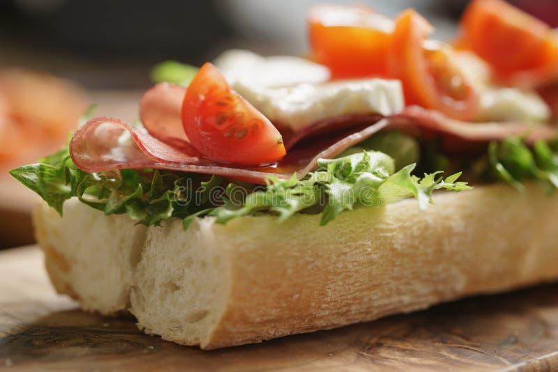 Bocadillo abierto con el prosciutto, la mozzarella y los tomates en la tabla de cocina imagen de archivo