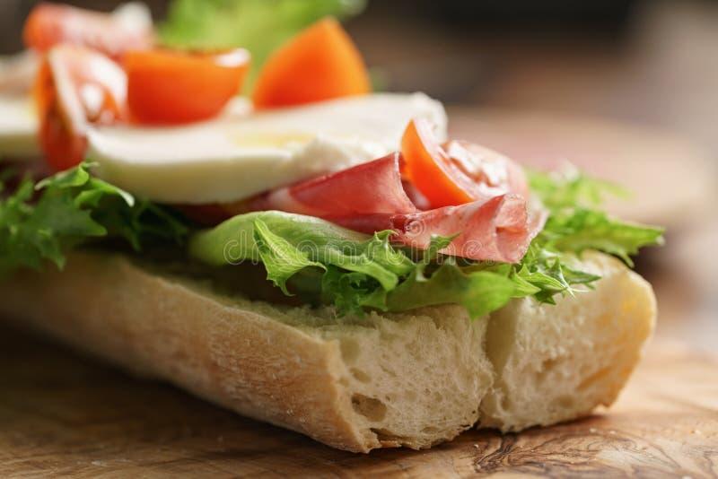 Bocadillo abierto con el prosciutto, la mozzarella y los tomates en la tabla de cocina fotografía de archivo libre de regalías