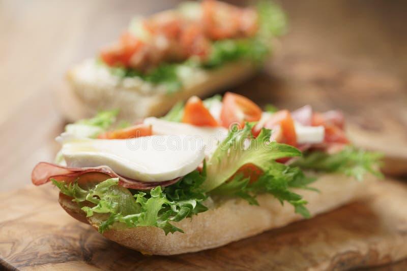 Bocadillo abierto con el prosciutto, la mozzarella y los tomates en la tabla de cocina imagen de archivo libre de regalías