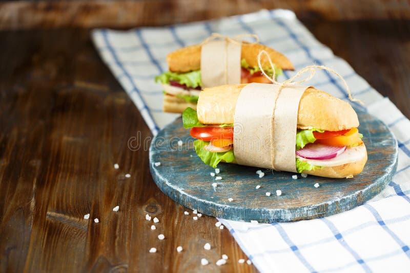 Bocadillo apetitoso del pan curruscante con el pollo, los tomates, la lechuga, el queso y las especias en un fondo de madera oscu imagen de archivo libre de regalías