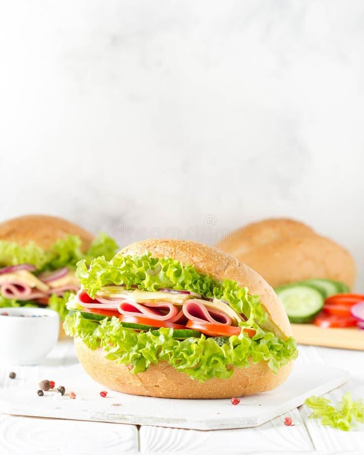 Bocadillo cerrado en bollo con el jam?n, queso, lechuga, tomate, pepino, cebolla roja Desayuno delicioso, almuerzo cl?sico fotos de archivo libres de regalías