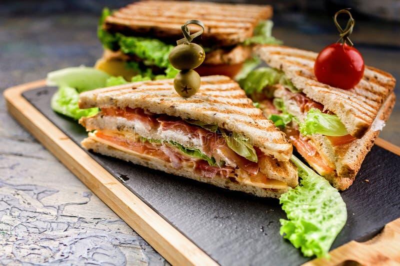 Bocadillo clásico de la tostada con carne de vaca ahumada, queso, los tomates y la lechuga Desayuno o almuerzo tradicional imagenes de archivo