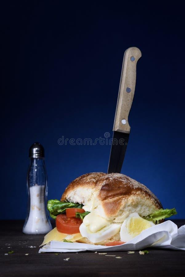 Bocadillo con el huevo, el tomate, la ensalada y el queso en una tabla de cortar fotos de archivo