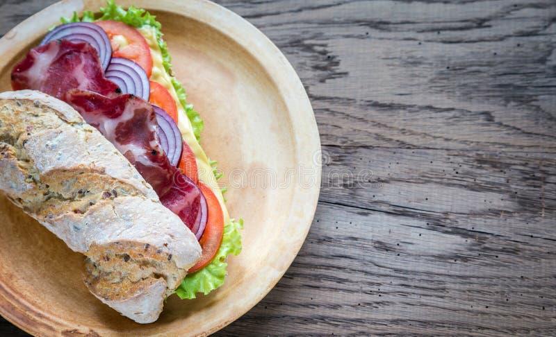 Bocadillo con el jamón, el queso y verduras frescas foto de archivo