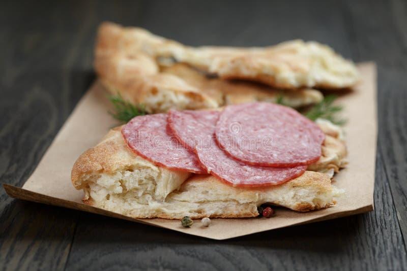 Bocadillo con el pan Pita y el salami en la tabla de madera imagen de archivo libre de regalías