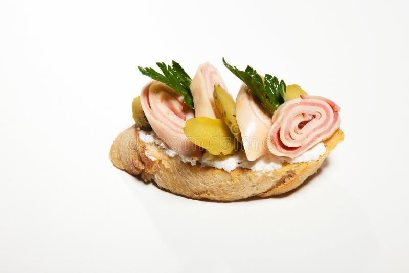 Bocadillo con el queso, el jamón, el pepino y el perejil blancos en el whi imagenes de archivo