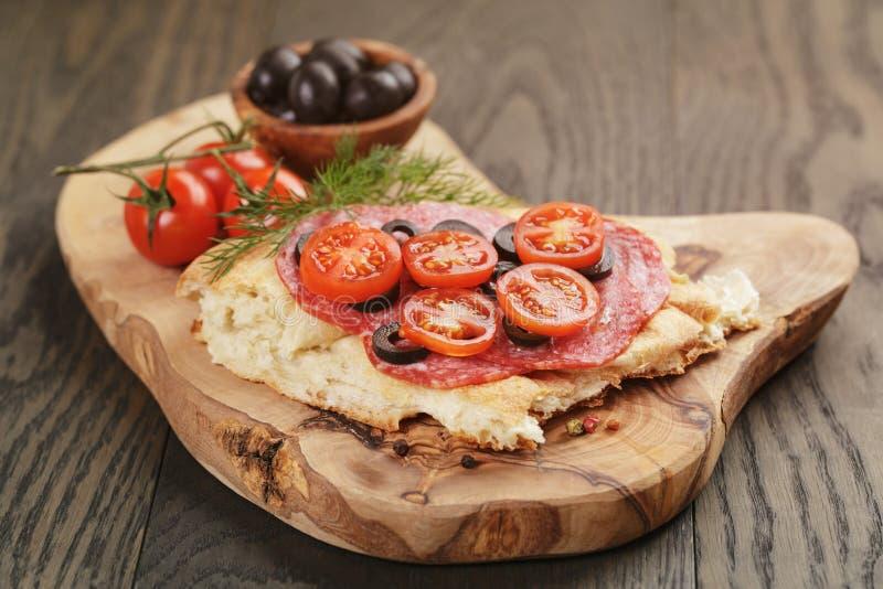 Bocadillo con el salami y las verduras del pan Pita encendido imagen de archivo
