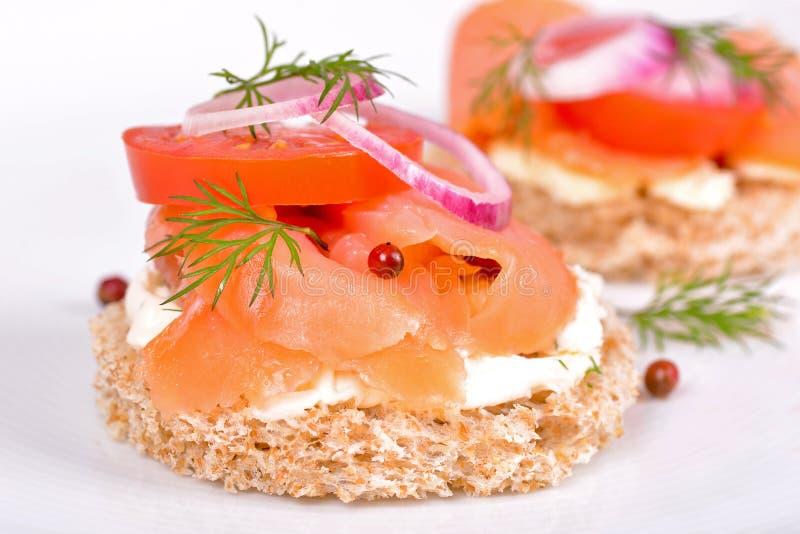 Bocadillo con el salmón ahumado y el tomate imagen de archivo