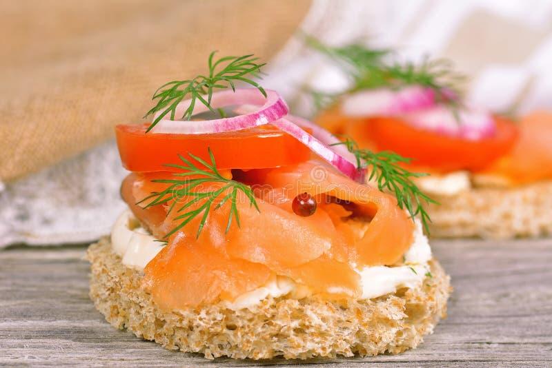 Bocadillo con el salmón ahumado y el tomate imágenes de archivo libres de regalías