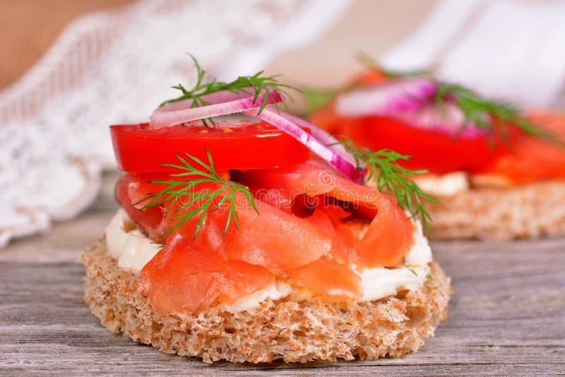 Bocadillo con el salmón ahumado y el tomate fotografía de archivo