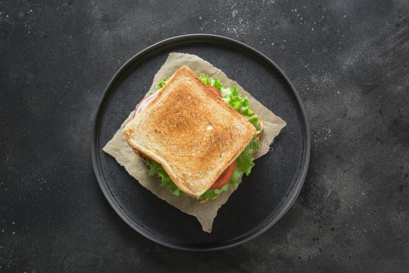 Bocadillo con el tocino, tomate, cebolla, ensalada en fondo negro Aislado Visión desde arriba imagen de archivo libre de regalías