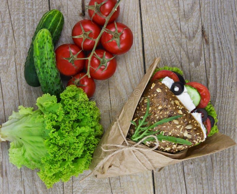 Bocadillo con la ensalada, el jamón, el queso y tomates en la tabla de madera T imagenes de archivo