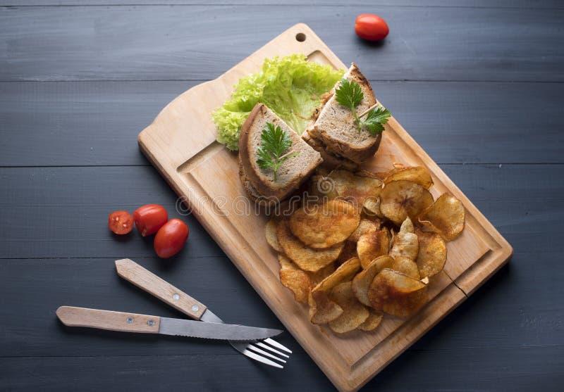 Bocadillo con las patatas del pollo y del ensalada y fritas en fondo de madera foto de archivo libre de regalías