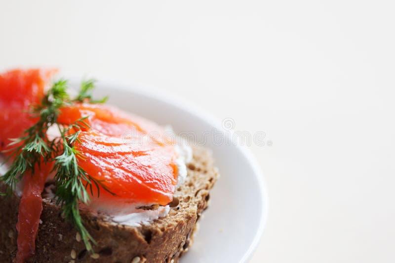Bocadillo con los salmones y el queso cremoso En un pedazo de pan del multi-grano del centeno fotos de archivo