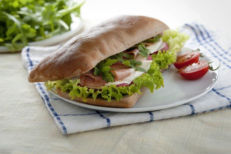 Bocadillo con pan, el jamón y la ensalada de la algarroba imagen de archivo