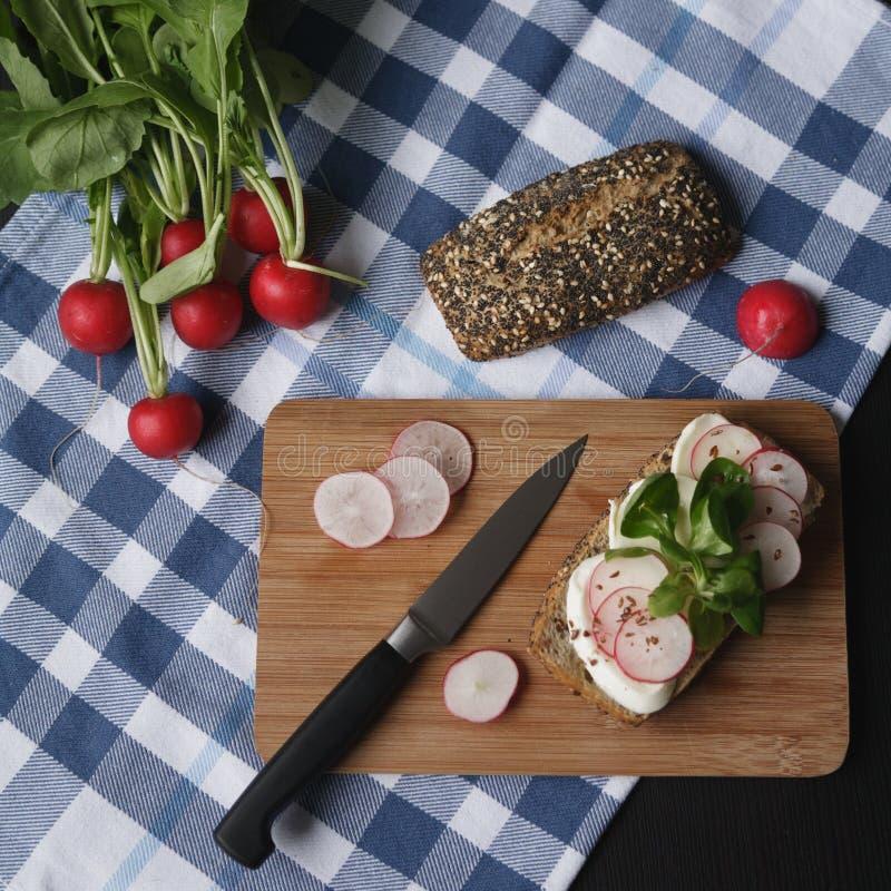 Bocadillo con queso del mozarella y el rábano de las rebanadas en tabla de cortar marrón de madera fotografía de archivo libre de regalías