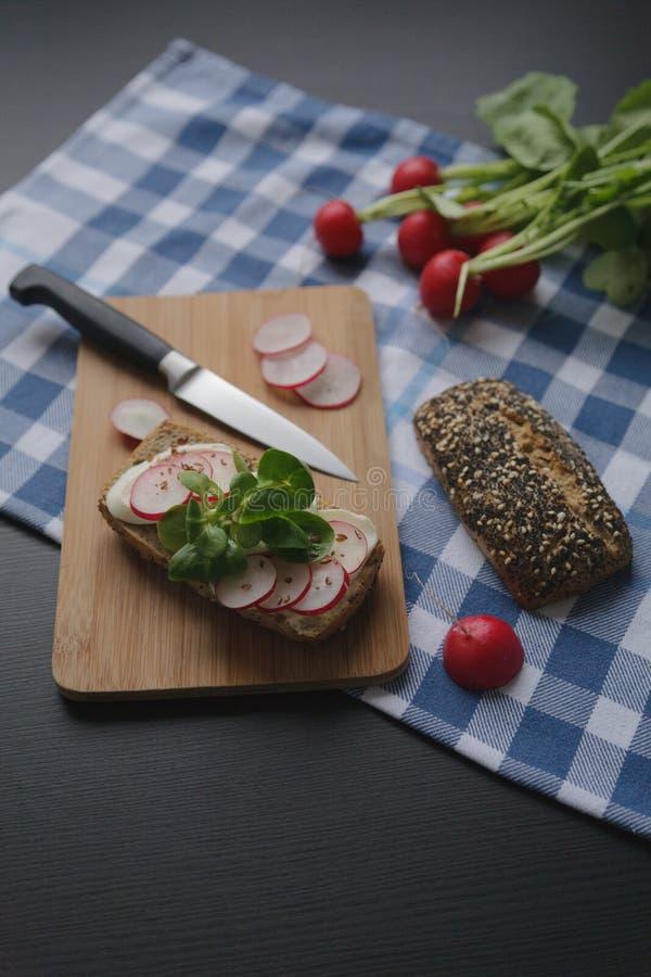 Bocadillo con queso del mozarella y el rábano de las rebanadas en tabla de cortar marrón de madera fotografía de archivo
