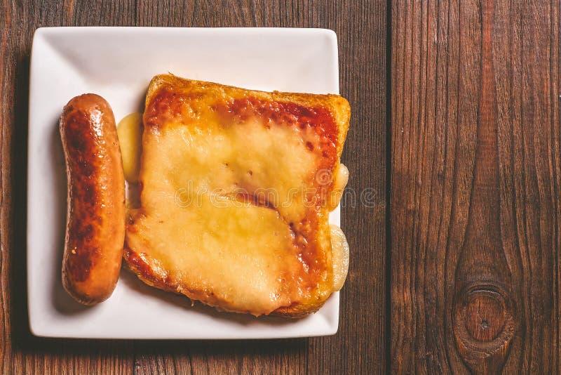 Bocadillo con queso derretido y el primer frito de la salchicha contra la perspectiva de un árbol oscuro imágenes de archivo libres de regalías