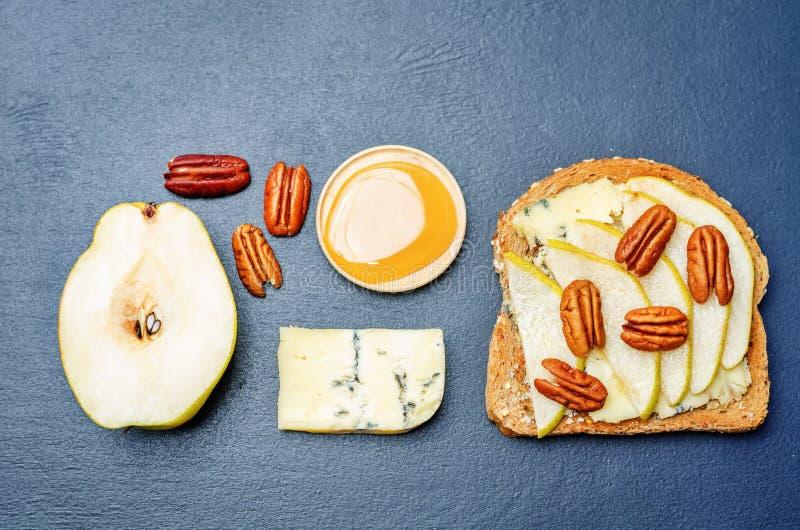Bocadillo con queso verde, la pera, la miel y la pacana fotos de archivo libres de regalías