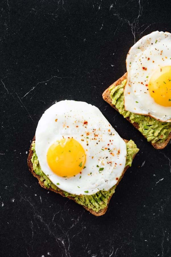 Bocadillo del desayuno con el huevo frito y el aguacate fotografía de archivo libre de regalías