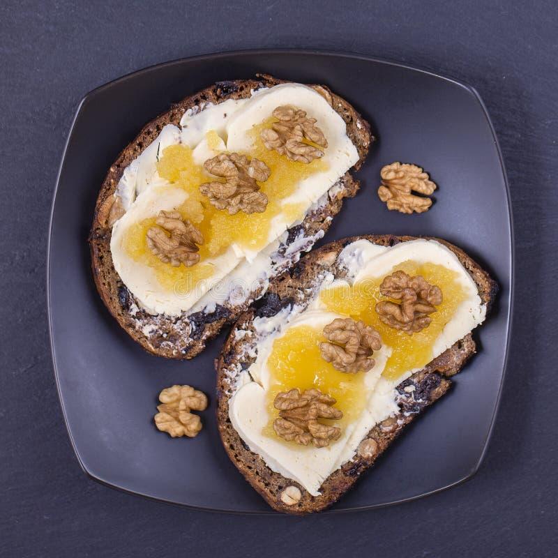 Bocadillo del pan ácimo con la mantequilla, el queso, la miel y las nueces, cierre para arriba fotografía de archivo