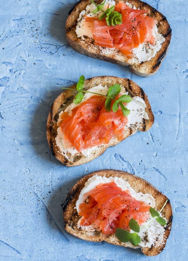 Bocadillo del salmón ahumado y del queso cremoso En un fondo azul, visión superior Aperitivos deliciosos con el vino fotografía de archivo