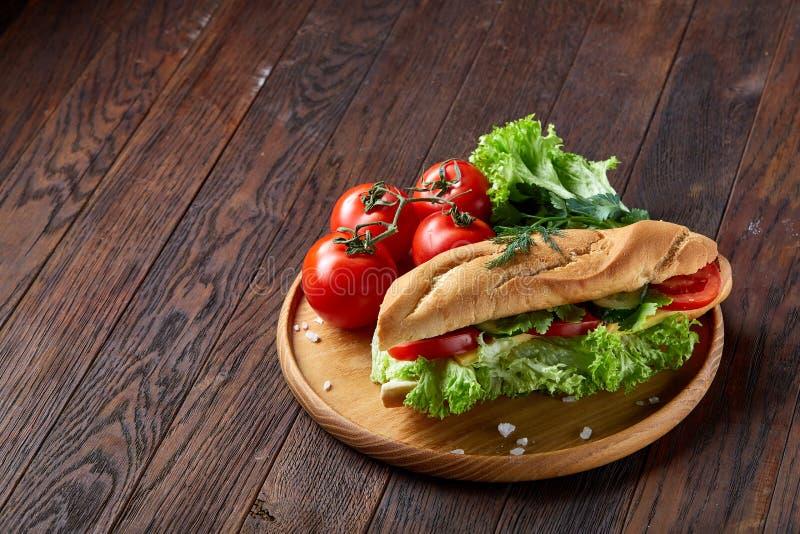 Bocadillo fresco con la lechuga, tomates, queso en la placa de madera, taza de café en el fondo rústico, foco selectivo imágenes de archivo libres de regalías