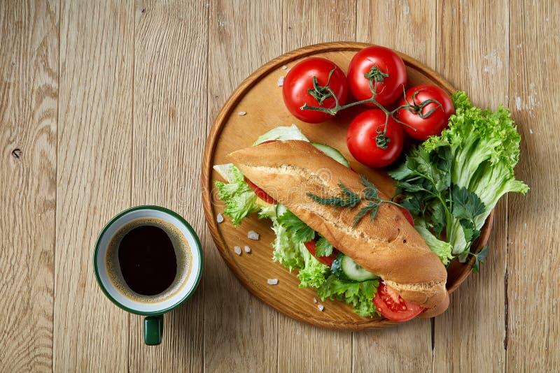 Bocadillo fresco con la lechuga, tomates, queso en la placa de madera, taza de café en el fondo rústico, foco selectivo foto de archivo