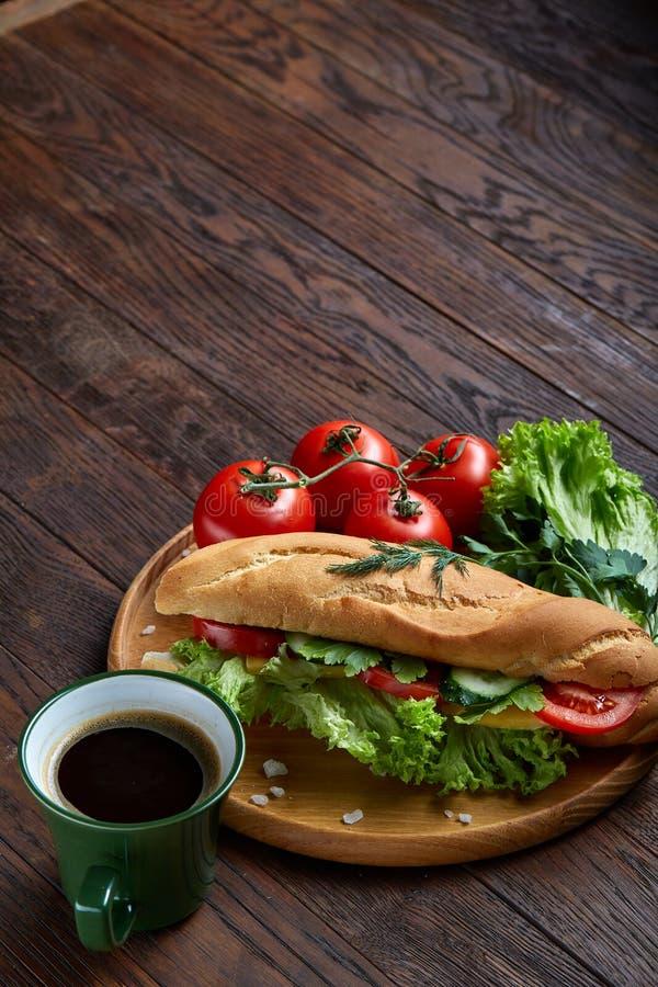 Bocadillo fresco con la lechuga, tomates, queso en la placa de madera, taza de café en el fondo rústico, foco selectivo fotografía de archivo libre de regalías