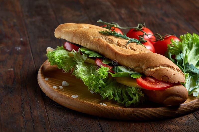 Bocadillo fresco con la lechuga, tomates, queso en la placa de madera, taza de café en el fondo rústico, foco selectivo imagen de archivo
