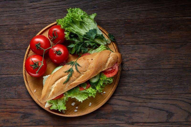 Bocadillo fresco con la lechuga, tomates, queso en la placa de madera, taza de café en el fondo rústico, foco selectivo fotos de archivo
