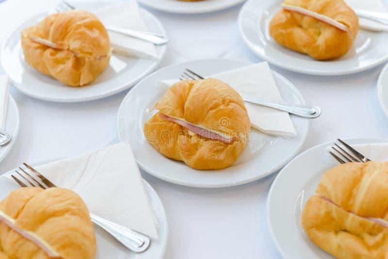 Bocadillo fresco del cruasán con el jamón y el queso en la placa blanca tiempo del té y descanso para tomar café en el negocio de imágenes de archivo libres de regalías
