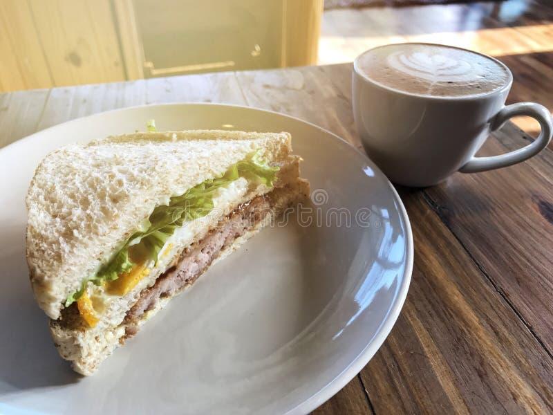 Bocadillo fresco y taza de café del arte del Latte en el plato blanco fotos de archivo
