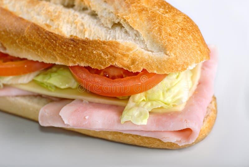 Bocadillo hecho en casa con el jamón, la ensalada, el chesse y los tomates en baguette del pan blanco fotografía de archivo