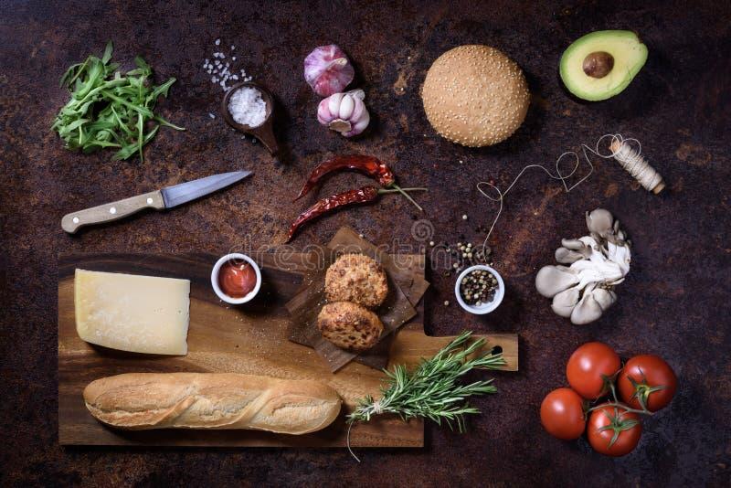 Bocadillo hecho en casa fresco en tablero oscuro de la porción con las verduras, el queso, la sal y las hierbas sobre fondo oscur fotografía de archivo