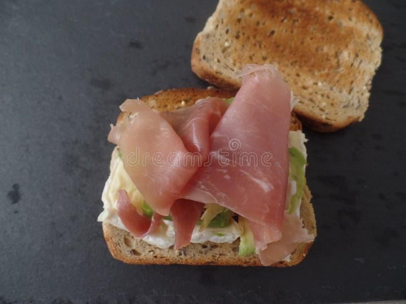 Bocadillo integral tostado con el aguacate, el queso y el jamón curado fotos de archivo