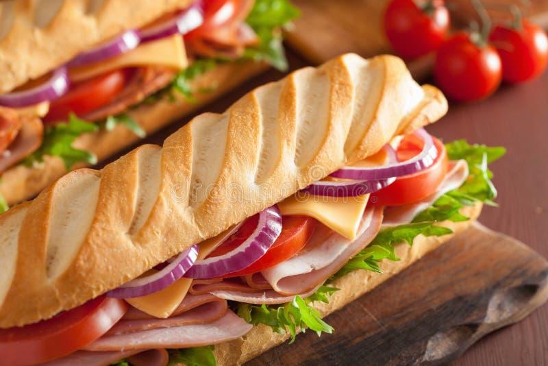 Bocadillo largo del baguette con el tomate y la lechuga del queso del jamón foto de archivo libre de regalías