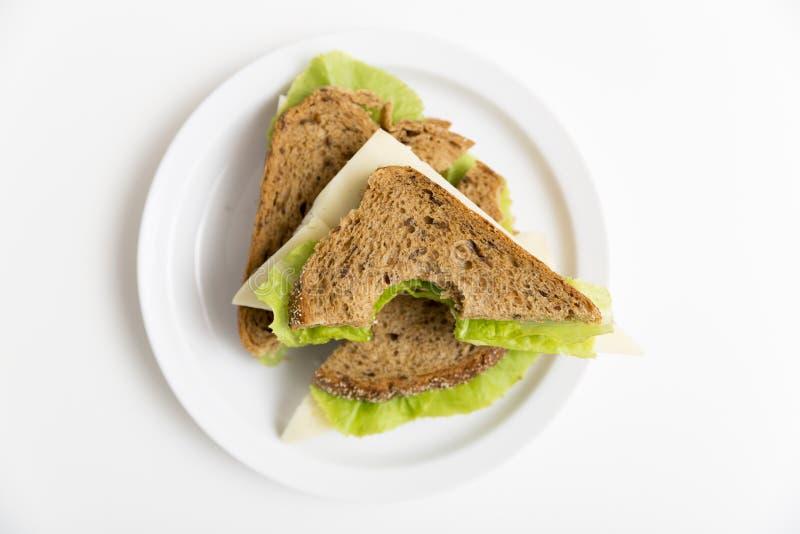 Bocadillo mordido del queso y de la lechuga en una placa blanca Almuerzo, brea imagenes de archivo