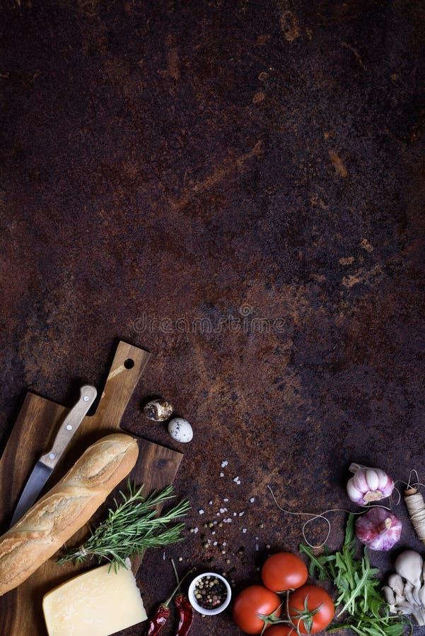 Bocadillo que cocina los ingredientes Baguette francés con queso y verduras sobre la encimera rústica Visión arriba, espacio de l foto de archivo libre de regalías