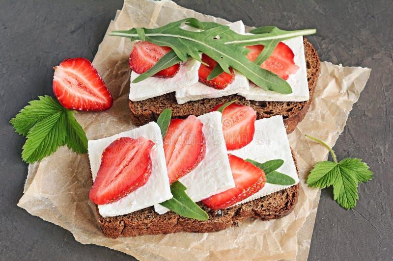 Bocadillo sano con pan de centeno, la fresa fresca, el arugula y el queso suave en el pergamino imágenes de archivo libres de regalías