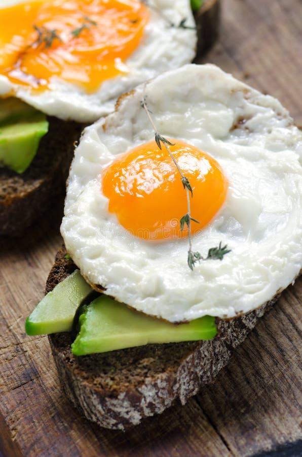 Bocadillo sano del desayuno con pan de centeno, el aguacate y los huevos fritos imagenes de archivo