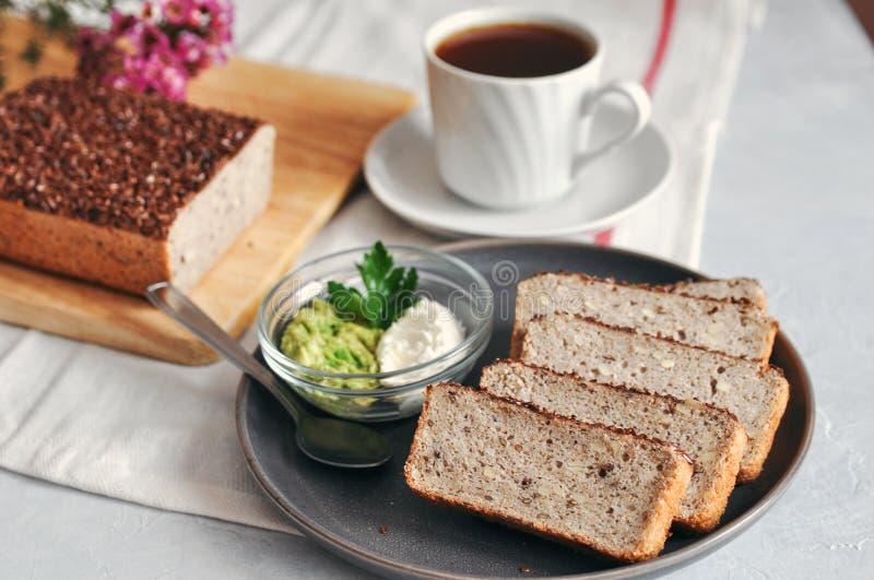 Bocadillo sano y apropiado del desayuno con el aguacate y el pan hecho en casa en el pan amargo del alforfón verde con las semill imagenes de archivo
