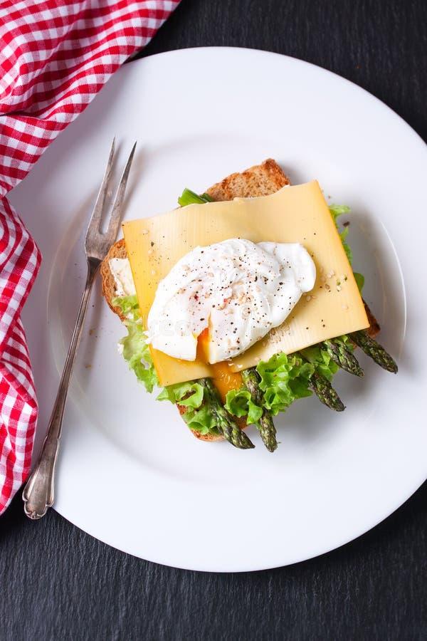 Bocadillo tostado con las hojas de la ensalada, el espárrago, el queso y el huevo escalfado imagen de archivo