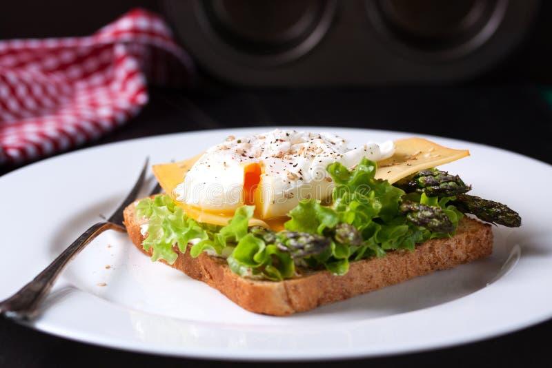 Bocadillo tostado con las hojas de la ensalada, el espárrago, el queso y el huevo escalfado fotografía de archivo libre de regalías