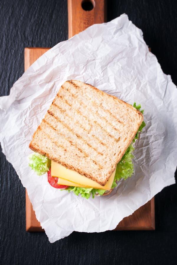 Bocadillo tostado con las hojas, los tomates y el queso de la ensalada con la bifurcación en una tabla de cortar en un fondo oscu imagen de archivo