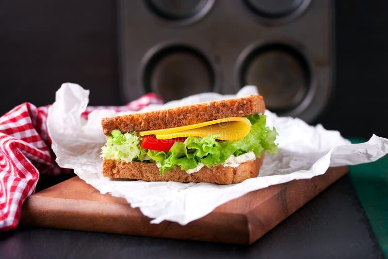 Bocadillo tostado con las hojas, los tomates y el queso de la ensalada con la bifurcación en una tabla de cortar en un fondo oscu fotos de archivo libres de regalías